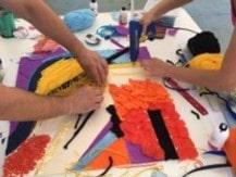 Partecipanti a lavoro su un'opera materica durante lo svolgimento di una attività di team building Art Experience della categoria Creative Team Building