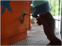 Partecipanti ad un Social Team Building decorano delle Arnie destinate ad avviare un centro di apicoltura in un'oasi del deserto.