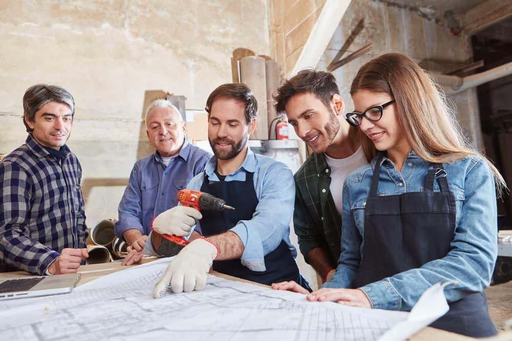 Un team studia il progetto di restauro di una casa famiglia organizzato da Made In Team come attività di team building