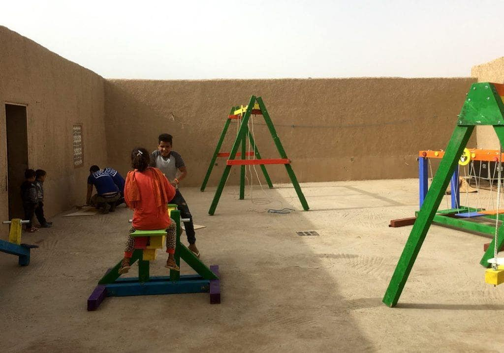 Bambini giocano nell'atrio della loro scuola con i giochi realizzati durante un Social Team Building Giochi per l'Africa organizzato da Made In Team in Italia
