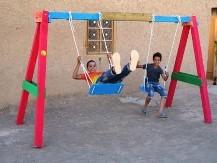 Bambini di un villaggio africano giocano su una altalena costruita durante un Social Team Building organizzato da Made In Team.
