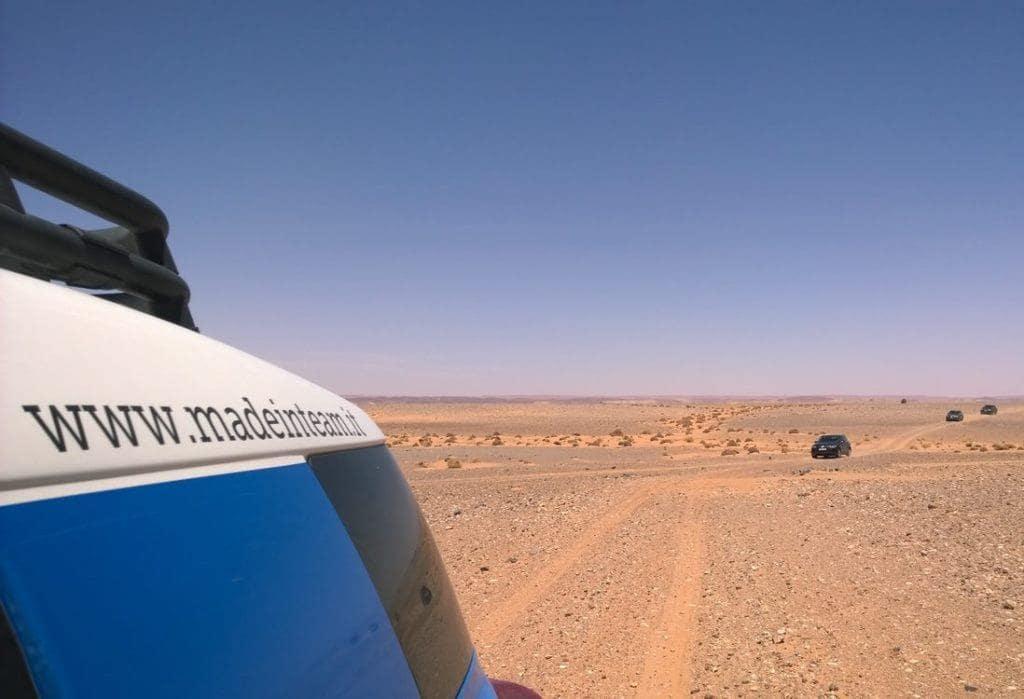 Un gruppo aziendale affronta le difficoltà del deserto a bordo di potenti fuoristrada per consegnare materiale scolastico ad una scuola dell'entroterra marocchino durante un Viaggio umanitario organizzato da Made In Team