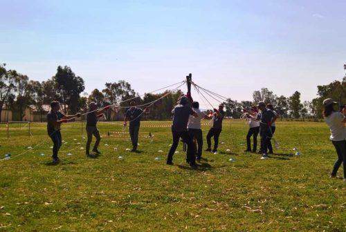 Team impegnati nell'affrontare l'esercizio dell'A-Frame durante un Soft Outdoor Team Building organizzato da Made In Team